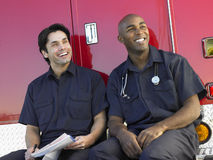 Two paramedics sitting by their ambulance stock photo