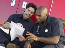 Two paramedics sitting by their ambulance Stock Photography