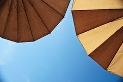Two parasols. Brown parasols under blue skies Royalty Free Stock Photography