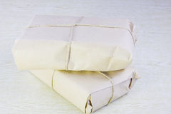 Two parcels bandaged by a rope. On a wooden surface Stock Photography