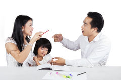 Two parents arguing near to their child. Two asian parents arguing together when help their daughter studying Royalty Free Stock Photo