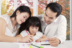 Two parents assist their child studying. Portrait of two parents give homeschooling education to their child at home Stock Image