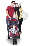 Two parents with baby in the stroller Stock Photo