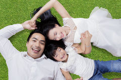 Two parents and child lying on grass Stock Photography