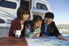 Two parents and daughter looking at map on picnic table outside RV Royalty Free Stock Photography