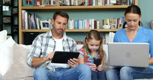 Two parents with her daughter using technologies. In the lounge stock video footage