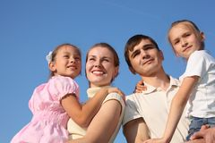 Two parents hold children on hands against sky royalty free stock images