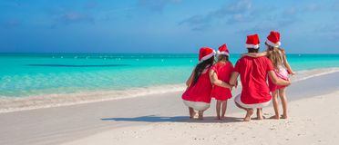 Two parents and kids in Santa Hat on white beach Royalty Free Stock Photo