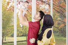 Two parents playing with their son near the window Royalty Free Stock Photo