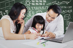 Two parents teach their child in the class Royalty Free Stock Photography