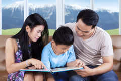 Two parents and their child read storybook Royalty Free Stock Photo