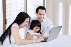 Two parents using laptop with daughter Stock Images