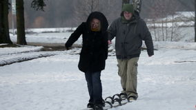 Two parents are walking on large skis without any hassle stock video