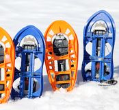 Two pari of modern snowshoes. Two pari of orange modern snowshoes in the mountain royalty free stock photos