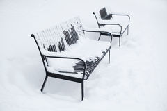 Two park benches covered with snow Stock Image