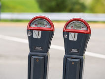 Two parking meter. Side by side of two red and gray parking meter Stock Photos