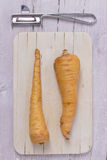 Two parsnips. On wooden board with a knife Royalty Free Stock Photography