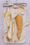 Two parsnips on wooden board. Partly peeled with a knife Stock Photography