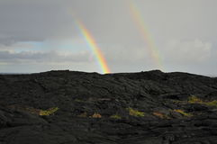 Two partial Rainbows and black lava Stock Image