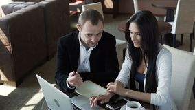 Two partner in workspace. Businesswoman and businessman teamwork. Two modern smiling partner concentration work in comfortable workspace on the table use the stock video footage