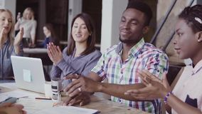 Two partners sign a contract, shake hands. Group of people clapping on a background at office. slow mo. Two partners, african and caucasian businessmen sign a stock video footage