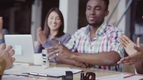 Two partners, african and caucasian sign a contract. Group of people clapping on a background at office. slow mo. Two partners, african and caucasian businessmen stock video