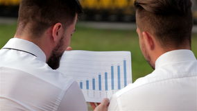 Two partners analyzing bar chart stock footage