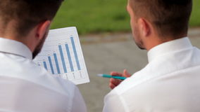 Two partners analyzing bar chart stock video footage