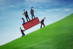 Two partners bringing boulder with business people. Image of busy business people above rock with two partners bringing a red boulder on the hill Royalty Free Stock Photography