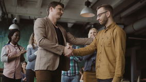 Two partners, businessman shake hands. Group of people clapping on a background. Manager congratulates trainee promotion