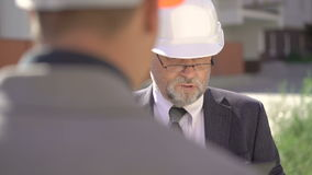 Two partners are discussing in construction helmets and using tablet. 4K.  stock footage
