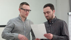 Two partners reading contract in the office. Professional shot on BMCC RAW with high dynamic range. You can use it e.g. in your commercial video, business stock video