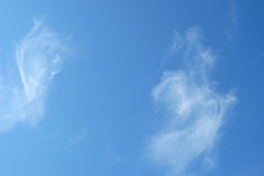 Two parts of heart shaped cloud. White clouds in blue sky Royalty Free Stock Image