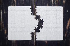 Two parts of a puzzle on dark wooden desk royalty free stock images