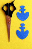 Two parts in the shape of an anchor cut from blue felt. The scissors on the yellow wool background. Step. Closeup. Top view Stock Photos