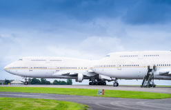 Two passenger airliners parked side by side on airport apron wir Stock Photography