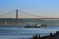 Two passenger boats Cacilheiros crossing the Tagus River in Lisbon, Portugal. With the 25 of April Bridge on the background Stock Photography