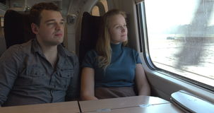 Two passengers looking out the train window stock video footage