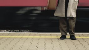 Train passengers different tracks. Two passengers about to take the train on different platforms. Low-angled point-of-view feet. Diegetic audio stock video footage