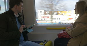 Two passengers in train using pad and smart watch. Male and female travelers going by train. Woman using smart watch while man working with tablet computer stock footage