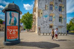 Two passersby and one advertising column in the center of Vilnius royalty free stock photography