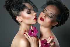 Two Passionate Women with Flowers Flirting. Couple of Tempting Passionate Women with Flowers Flirting royalty free stock photos