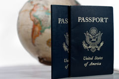 Two passports and a globe. Two passports, one well used one in front of a globe or planetarium Stock Photography