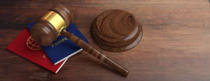 Two passports and a judge gavel on wooden desk background. 3d illustration royalty free stock photo