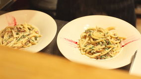 Two pasta dishes decorated before served stock video