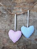 Two pastel pink and blue textile hearts against wooden background. Two pastel blue and pink textile or fabric hearts hanging on a rope or string against rustic stock image