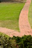 Two paths into one. Two red stone paths converges into one amid the grass and plants in Presidio park Stock Image