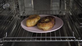 Two patties in the oven. On pink plate stock footage