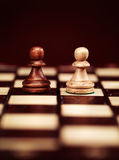 Two pawns on chessboard. Two pawns chess pieces on a chessboard, concept Royalty Free Stock Image