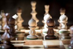 Two pawns face off in a game. Two pawns on a chessboard face off with other pieces around them Stock Photos